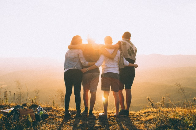 Foto de amigos abrazados, vistos desde espaldas, se encuentran frente al sol en un atardecer