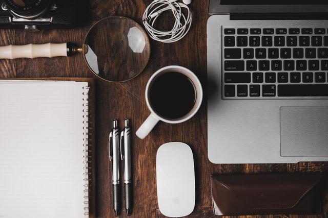 Escritorio muy ordenado, donde se ve una notebook, un café, lapiceras y cuaderno acomodados y una lupa