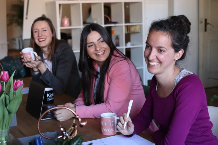 Tres personas sonriendo en su escritorio