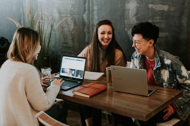 personas compartiendo un escritorio y riendo