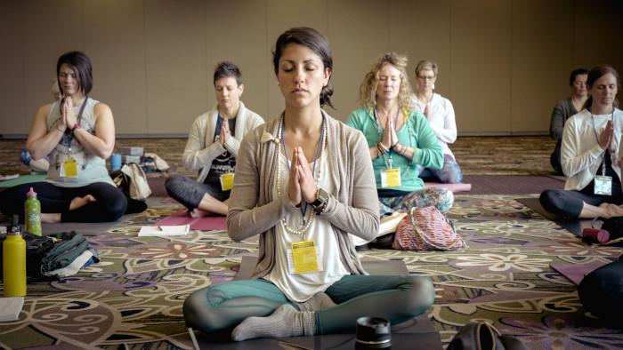 personas meditando sentadas en el piso