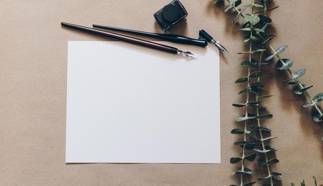 Imagen de papel en blanco, plumas para escribir y hojitas a un costado